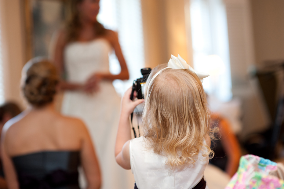 flower girl taking picture of bride