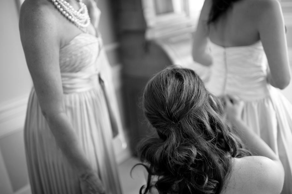 Maid of honor helping bride get dressed