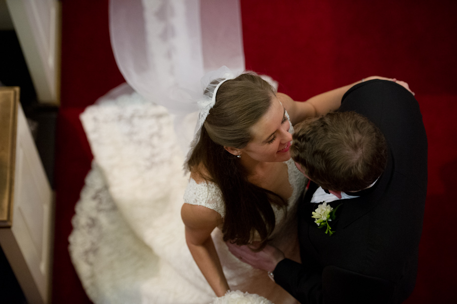 Bride and groom kissing at the end of the aisle