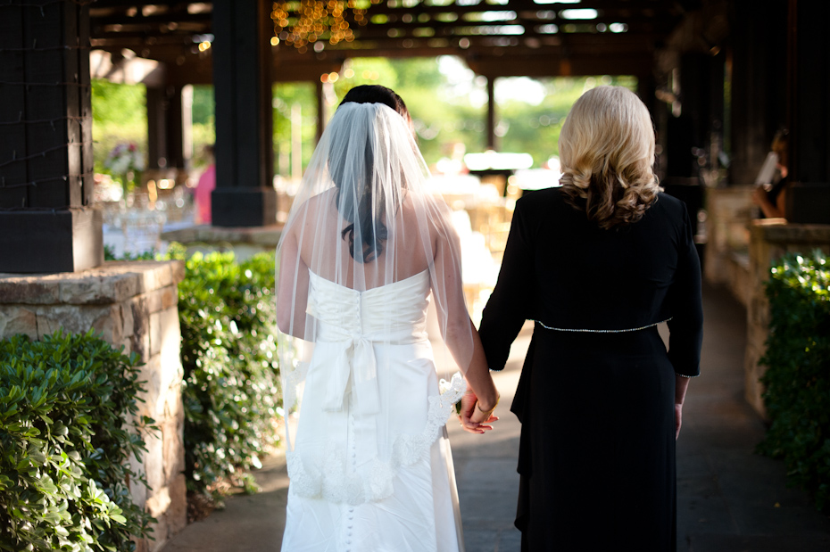 Mom holding hands with bride